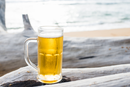 Glass mug of beer on a beach at sunset