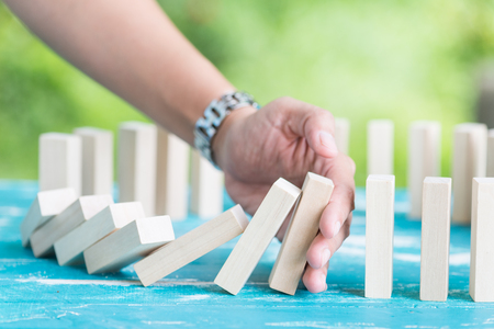 Solution concept with hand stopping wooden blocks from falling in the line of domino Standard-Bild