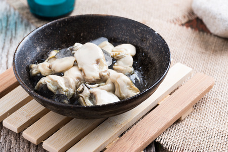 expensive: Opened Oysters on dark bowl on  wooden background