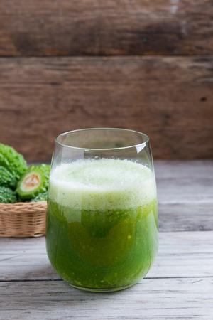 Herbal juice of green momodica , Balsam apple, Balsam pear, Bitter cucumber , Bitter gourd , Stuffed bitter gourd, karela in a glass with sliced vegetables, karela juice or bitter gourd juice