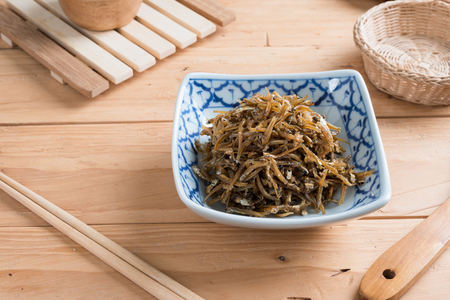 Fried sweet Anchovies in bowl on wooden background