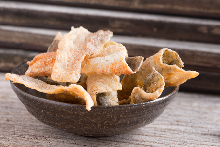 brown trout: Crispy fried salmon skin on  wooden table background Stock Photo