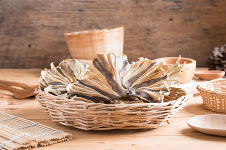 Raw dried sundried stingray radiating circular fish on wooden background