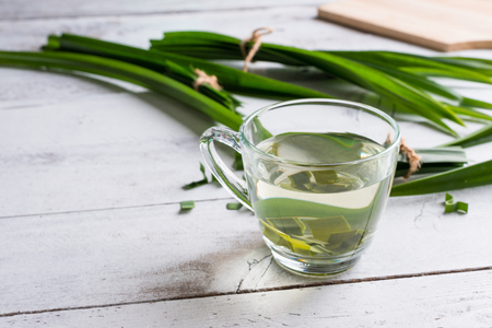 Fresh Fragrant Pandan Tea and leaves on white wood background