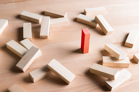 Business concept metaphor to able to survive or dominant from other . One  wood block standing and outstanding among the collapse of other wood block. Stock Photo