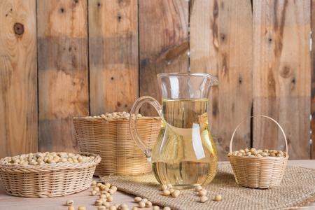 Sojabonen in mandje en sojabonenolie in pot op houten achtergrond Stockfoto