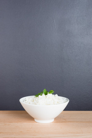 Steamed rice on white bowl wooden background