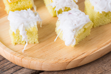 Coconut cake on wooden plate on wooden background. Stock Photo
