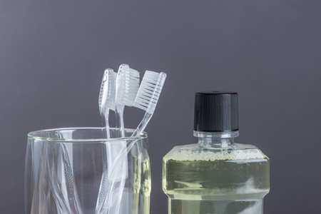 New Toothbrush  in glass and mouthwash  on gray background Stock Photo