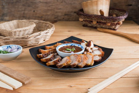 Deep Fried Crispy Pork Belly Cooked with Garlic and spicy dipping sauce on wooden table background
