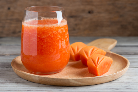 Fresh papaya smoothie juice in glass on wooden background