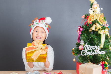 Happy asian thai child girl age 6 year with Christmas gifts near a Christmas tree Stock Photo