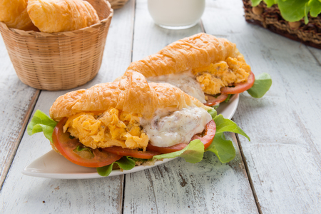 Breakfast Croissant stuffed scrambled eggs and tuna on wooden background