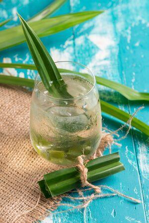 Fresh Fragrant Pandan Tea nad leaves on green wood background