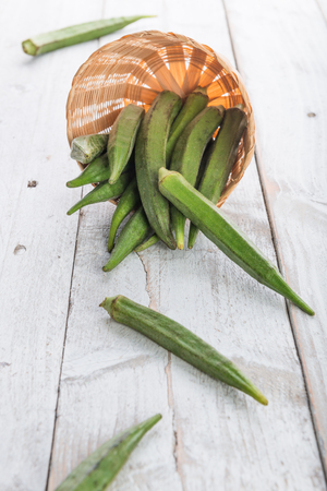 Fresh Green Okra ( Abelmoschus esculentus ) on white wooden background