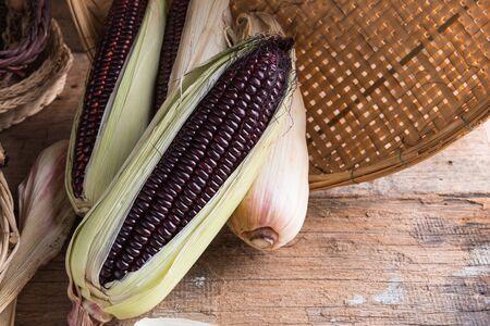 Fresh purple corn on wooden background Фото со стока
