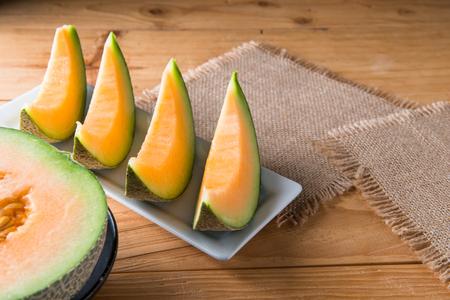 Melone Scheibe auf Holztisch Hintergrund Standard-Bild