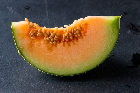 Melon slice on rock plate background Stock Photo