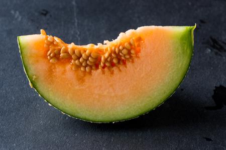 Melon slice on rock plate background Standard-Bild