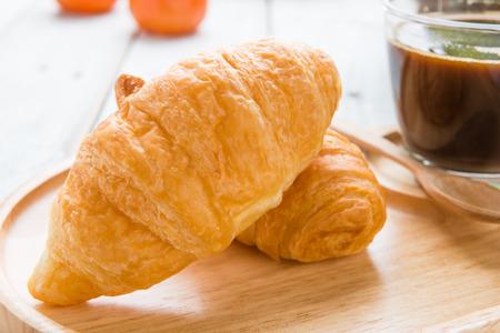 Tasty croissants on white wooden background