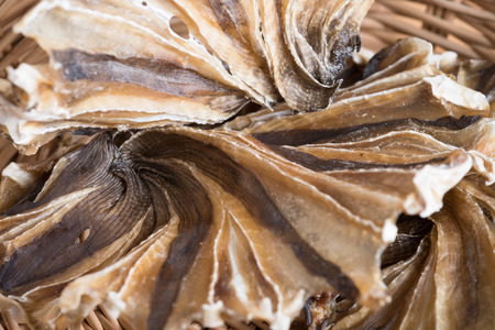 Raw dried sundried stingray radiating circular fish on wooden background, thai traditional food preservation