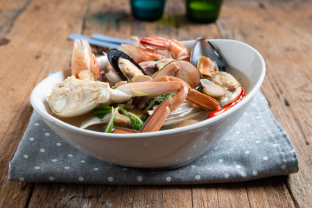 Spicy Seafood Soup on white dish , thai cuisine , wooden background