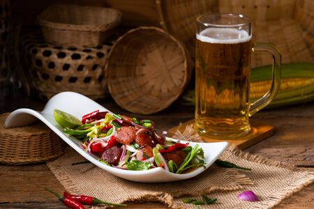 Spicy Chinese pork sausage with vegetable Thai salad in white plate on wooden background