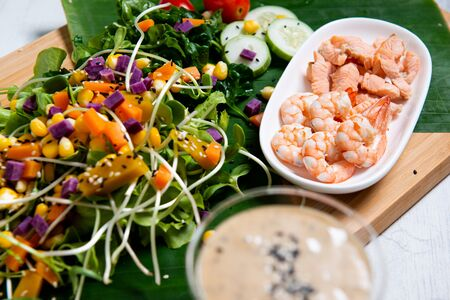Fresh salad plate with shrimp, salmon, tomato and mixed greens  on wooden background close up. Healthy food. Clean eating.