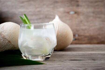Fresh coconut juice in a glass with coconut white meat and peeled coconut on wood background. Фото со стока