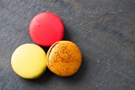 Pile of sweet and colorful french macaroons on dark rock background. 스톡 콘텐츠