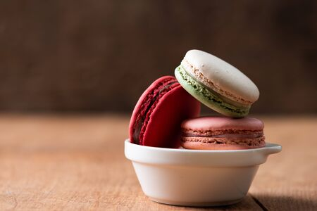 Pile of sweet and colourful french macaroons on wooden background. 스톡 콘텐츠