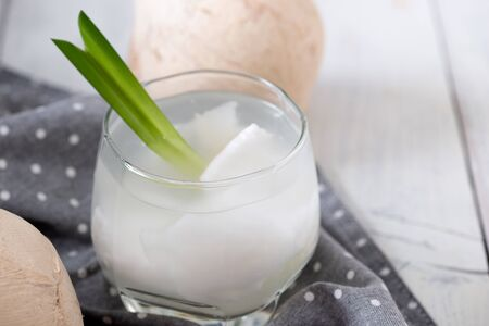 Fresh coconut juice in a glass with coconut white meat and peeled coconut on wood background. 스톡 콘텐츠