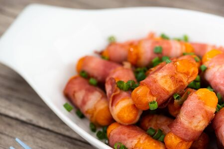 Mini sausages wrapped in smoked bacon .