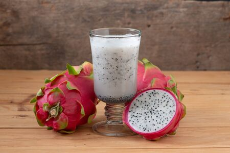 Fresh Dragon fruit smoothie on wooden table.