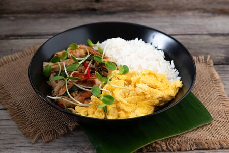 Rice topped with stir-fried shrimp and basil, and fried eggs in white dish. Thai street food. Stockfoto