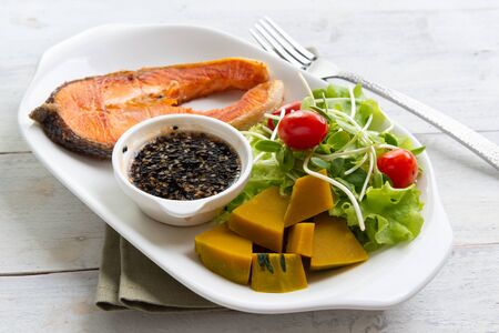 Grilled Salmon with Fresh Salad Leaf on white plate