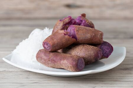 Steamed purple sweet potato in white plate eat with sugar and coconut