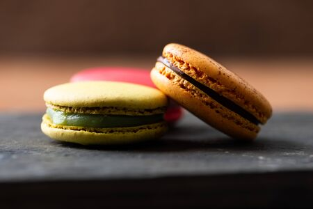 Pile of sweet and colorful french macaroons on wooden background.