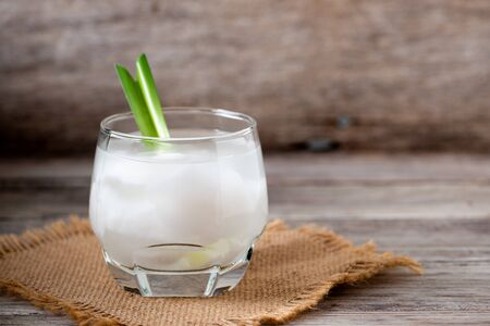 Fresh coconut juice in a glass with coconut white meat and peeled coconut on wood background. Banco de Imagens