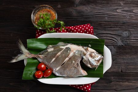 Steamed fish with spicy sauce,  Thai food, on dark wood background textures. low fat food for diet, Stock Photo