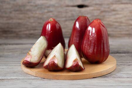 Owocowe aromaty róży tajlandzkiej o słodkim czerwonym połysku. Różowe jabłko na tle drewna Zdjęcie Seryjne