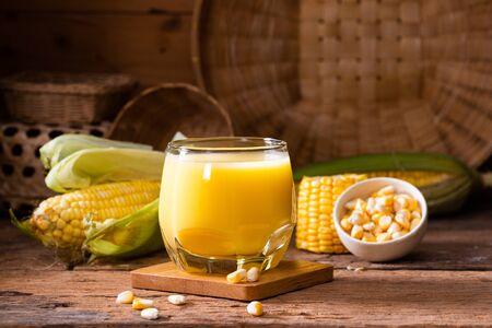 Fresh sweet corn juice (corn milk) and corn on wooden background
