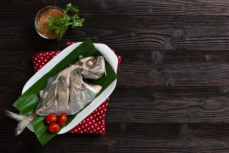 Steamed fish with spicy sauce,  Thai food, on dark wood background textures. low fat food for diet, Banco de Imagens
