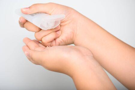 Hands Applying Sanitizer Gel. hands using wash hand sanitizer gel dispenser, against Novel coronavirus or Corona Virus Disease (Covid-19) at public train station. Antiseptic, Hygiene and Healthcare concept