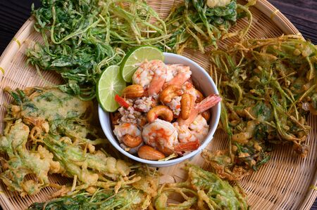 Crispy deep fried morning glory with spicy shrimp salad. wood background