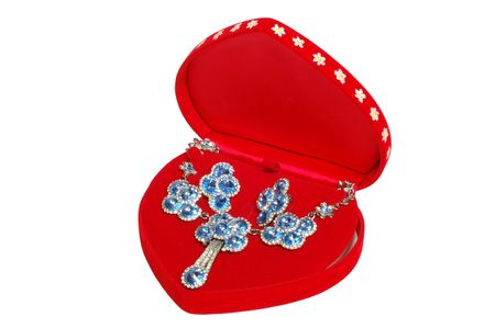 Blue jewelry in red open box, isolated on white photo