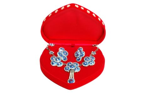 Red jewelry box with blue stones necklace and earrings, isolated on white photo