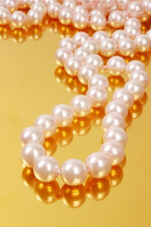 perle rose: Pink pearl necklace on gold background Banque d'images