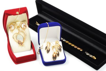 Gold jewelry sets inside a boxes, on white background photo