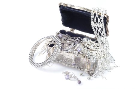 a bracelet: Metal jewelry open box with accessory on whitee background